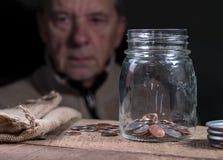 Kaukasischer Mann des Seniors im Ruhestand, der restliche Einsparungen betrachtet stockfotografie
