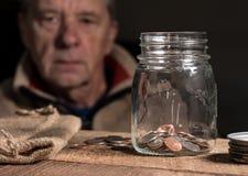 Kaukasischer Mann des Seniors im Ruhestand, der restliche Einsparungen betrachtet lizenzfreie stockbilder
