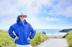 Kaukasischer Mann in die Vierziger, die Regenjacke durch Ozeanufer tragen Lizenzfreie Stockbilder