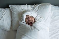 Kaukasischer Mann gerollt in der weißen Decke Lizenzfreie Stockfotos