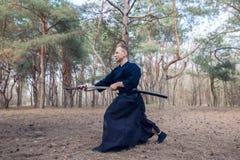 Kaukasischer Mann mit einer japanischen Klinge, ein katana, das Iaido übt Lizenzfreies Stockfoto