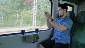 Kaukasischer Mann reist in einen Zug Macht Fotos der Natur auf einem mobilen Smartphone Langsame Bewegung stock video