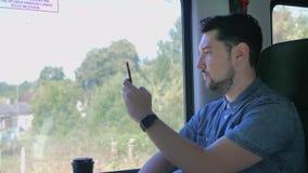 Kaukasischer Mann reist in einen Zug Macht Fotos der Natur auf einem mobilen Smartphone Zeitlupe-nahes hohes stock footage