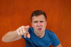 Kaukasischer Mann unbefriedigtes Stirnrunzeln Seinen Finger voran stoßen lizenzfreies stockbild