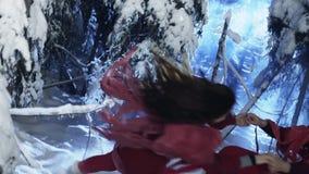 Kaukasischer Mann und die Frau, die in der roten Kleidung gekleidet wird, tanzen in Holz des verschneiten Winters stock video