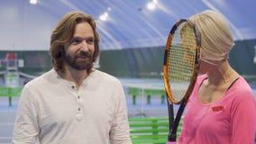 Kaukasischer Mann und Frau spricht am Tennisplatz stock video