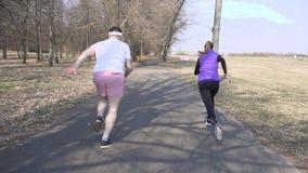 Kaukasischer Mann und Freundinnen bilden im Frühjahr Park, Sport zu spielen und ein Rennen, Marathon, Zeitlupe laufen zu lassen a stock footage