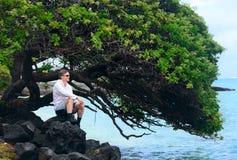 Kaukasischer Mann in Vierziger auf felsigem hawaiischem Ufer Lizenzfreies Stockfoto