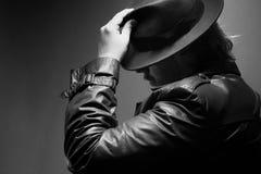 Kaukasischer Mann in Weinlese Regenmantel und Fedora Schwarzweiss-Hand auf Hut stockfotos