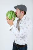 Kaukasischer Mannkuß eine Wassermelone Stockfotos