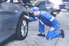 Kaukasischer Mechaniker, der auf einem Reifen in einer Werkstatt überprüft lizenzfreies stockfoto