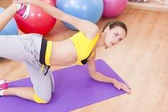 Kaukasischer sexy weiblicher Athlet In Good Fit, welches das Bein und Hände ausdehnen Übungen tut Stockfoto