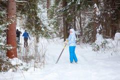 Weiblicher Skifahrer, der zurück beim Ski fahren im Winterwald schaut Stockfoto