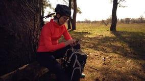 Kaukasischer Sportradfahrer-Frauensport weg vom Rennradpark nahe Baum Sportlerin in der Sportkleidung und Sturzhelm und Schwarzes stockfoto