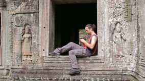 kaukasischer Tourist, der Handy im angkor verwendet stock video
