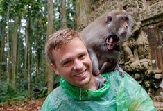 Kaukasischer Tourist im grünen Regenmantel mit wildem Affen auf seiner Schulter Lizenzfreies Stockfoto