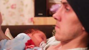 Kaukasischer Vater setzt sein Kind, um zu schlafen das Kind liegt auf dem Vater s-Kasten, denmann Telefon in seinen Händen hält u stock video footage
