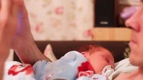 Kaukasischer Vater setzt sein Kind, um zu schlafen das Kind liegt auf dem Vater s-Kasten, denmann Telefon in seinen Händen hält u stock video