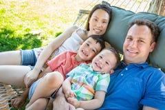 Kaukasischer Vater und chinesische Mutter, die in der H?ngematte mit Mischung sich entspannt lizenzfreies stockbild