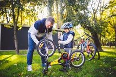 Kaukasischer Vati des Vatertags und jähriger Sohn 5 im Hinterhof nahe dem Haus auf dem grünen Gras auf dem Rasen, der ein Fahrrad stockfotografie