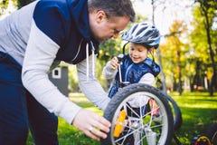 Kaukasischer Vati des Vatertags und jähriger Sohn 5 im Hinterhof nahe dem Haus auf dem grünen Gras auf dem Rasen, der ein Fahrrad lizenzfreie stockbilder