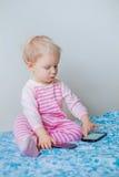 Kaukasisches blondes Baby, das einen Anruf, spielend mit Mobilhandy mit lustigem Ausdruck auf Gesicht macht Lizenzfreie Stockbilder