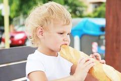Kaukasisches blondes Baby, das französisches Stangenbrot isst Lizenzfreie Stockfotografie