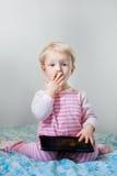 Kaukasisches blondes Baby, das im Bett spielt mit digitaler Tablette mit lustigem Gesichtsausdruck sitzt Stockbild