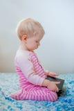 Kaukasisches blondes Baby, das im Bett spielt mit digitaler Tablette mit lustigem Gesichtsausdruck sitzt Lizenzfreie Stockbilder