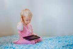 Kaukasisches blondes Baby, das im Bett spielt mit digitaler Tablette mit lustigem Gesichtsausdruck sitzt Lizenzfreie Stockfotografie