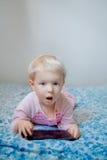 Kaukasisches blondes Baby, das im Bett spielt mit digitaler Tablette mit lustigem Gesichtsausdruck sitzt Lizenzfreie Stockfotos