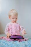 Kaukasisches blondes Baby, das im Bett spielt mit digitaler Tablette mit lustigem Gesichtsausdruck sitzt Stockfotografie