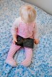 Kaukasisches blondes Baby, das im Bett spielt mit digitaler Tablette sitzt Stockbilder
