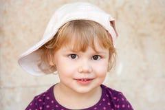 Kaukasisches blondes Baby in der weißen Baseballmütze Lizenzfreie Stockfotografie