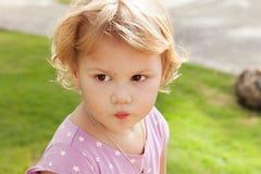 Kaukasisches blondes Baby in einem Park, Porträt Stockfotos
