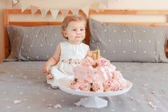 Kaukasisches blondes Baby im weißen Kleid ihren ersten Geburtstag feiernd Stockfotos