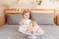 Kaukasisches blondes Baby im weißen Kleid ihren ersten Geburtstag feiernd Stockbild