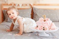 Kaukasisches blondes Baby im weißen Kleid ihren ersten Geburtstag feiernd Lizenzfreie Stockfotografie
