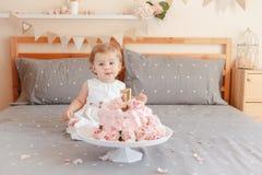 Kaukasisches blondes Baby im weißen Kleid ihren ersten Geburtstag feiernd Stockfotografie
