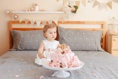 Kaukasisches blondes Baby im weißen Kleid ihren ersten Geburtstag feiernd Stockfoto