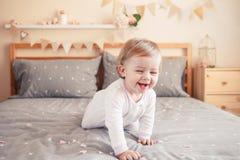 Kaukasisches blondes Baby im weißen onesie, das auf Bett im Schlafzimmer sitzt Lizenzfreies Stockfoto
