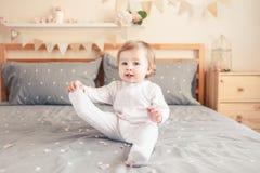 Kaukasisches blondes Baby im weißen onesie, das auf Bett im Schlafzimmer sitzt Stockfoto