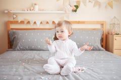 Kaukasisches blondes Baby im weißen onesie, das auf Bett im Schlafzimmer sitzt Stockfotos