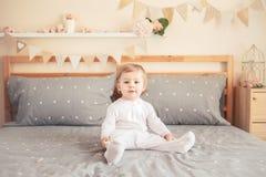 Kaukasisches blondes Baby im weißen onesie, das auf Bett im Schlafzimmer sitzt Lizenzfreie Stockfotos