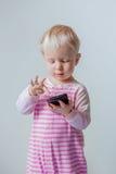 Kaukasisches blondes Baby mit den blauen Augen, die einen Anruf, spielend mit Mobilhandy machen Lizenzfreie Stockfotografie