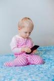 Kaukasisches blondes Baby mit den blauen Augen, die einen Anruf, spielend mit Mobilhandy machen Lizenzfreies Stockbild