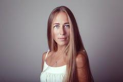 Kaukasisches blondes junges schönes Mädchenfrauenmodell mit dem langen Haar und den blauen Augen im weißen Kleid Lizenzfreie Stockfotos