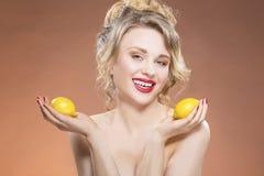 Kaukasisches blondes Mädchen, das mit zwei Zitronen in den Händen aufwirft Stockfoto