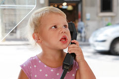 Kaukasisches blondes Mädchen, das am Straßentelefon spricht Lizenzfreies Stockfoto