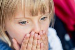 Kaukasisches blondes Mädchen des jungen Babys mit den Händen ausführlich Gesicht Stockfotografie